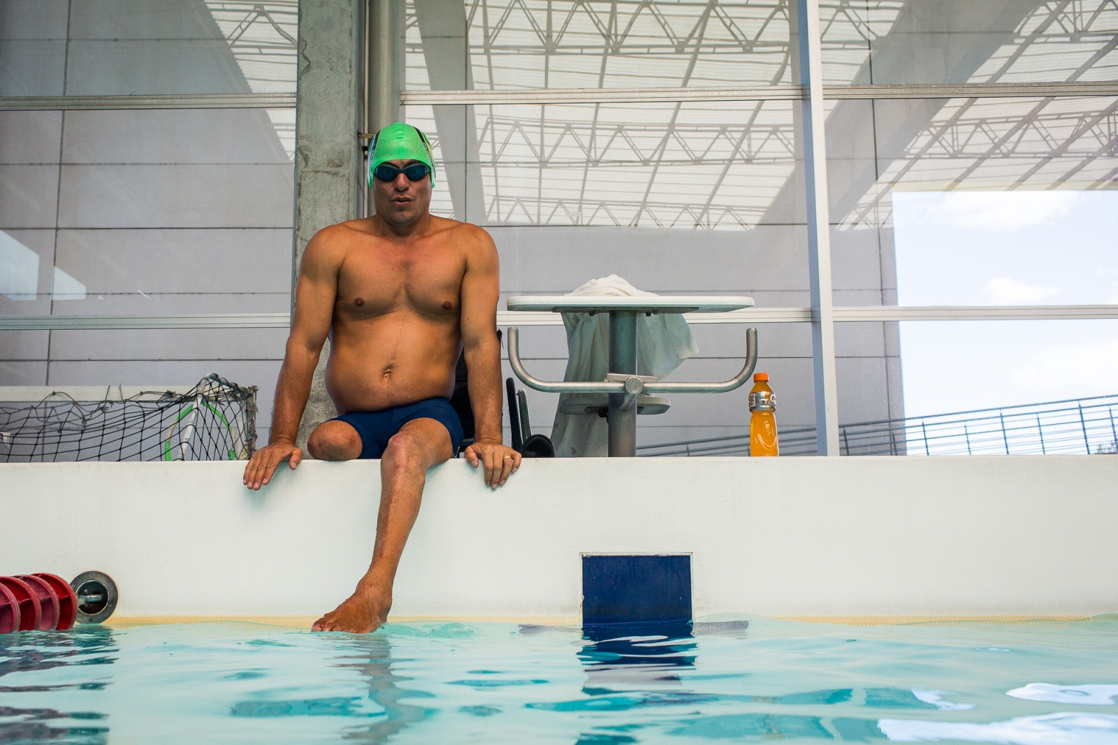 Moises Fuentes Garcia, 41, sits on the border of the swimming pool, before the beginning of his training session at the Simon Bolivar Aquatic Complex, Bogotá, 4th June, 2016.