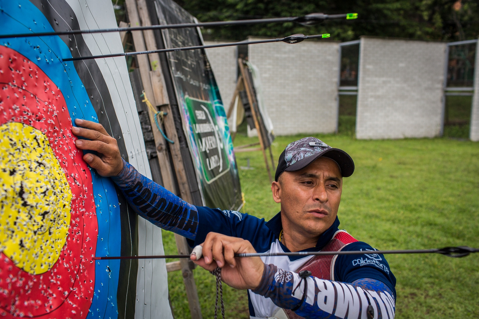 German Gomez, 49, collects the arrows from the target sign during a practice session at the Belen Sports Complex, Medellin, 28th April, 2016.