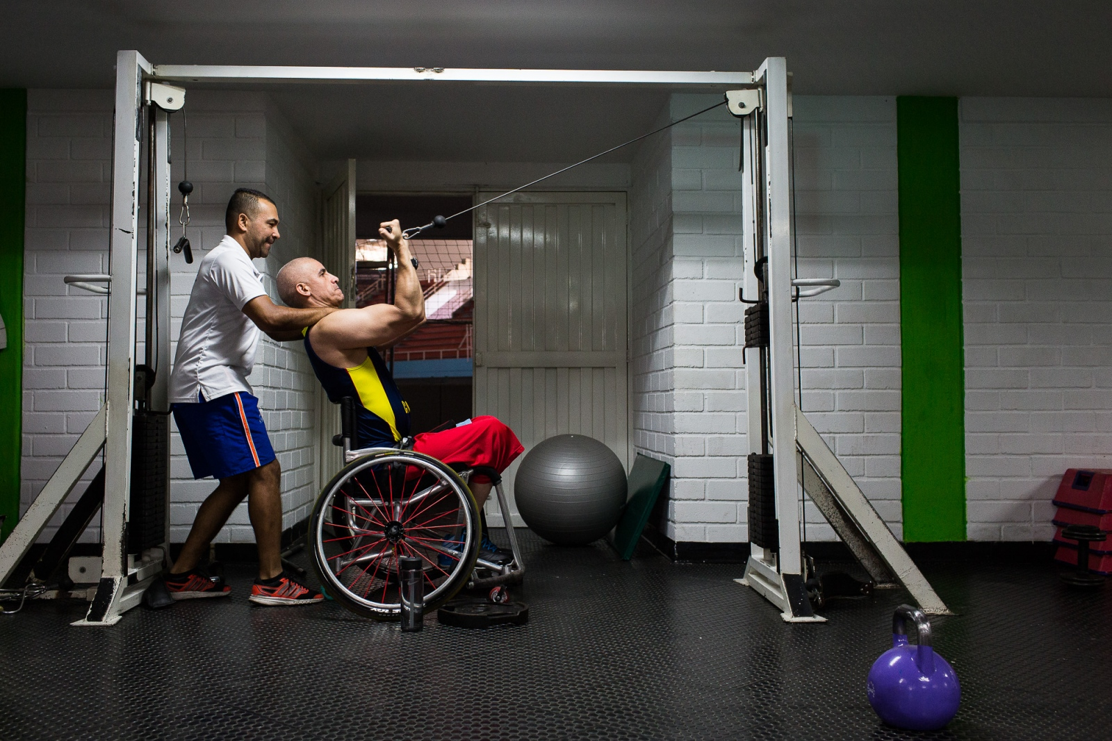 Oscar Rios, 42, does exercises with the help of his fitness coach on the Envigado Gymnasium, Medellin, 23rd March, 2016.