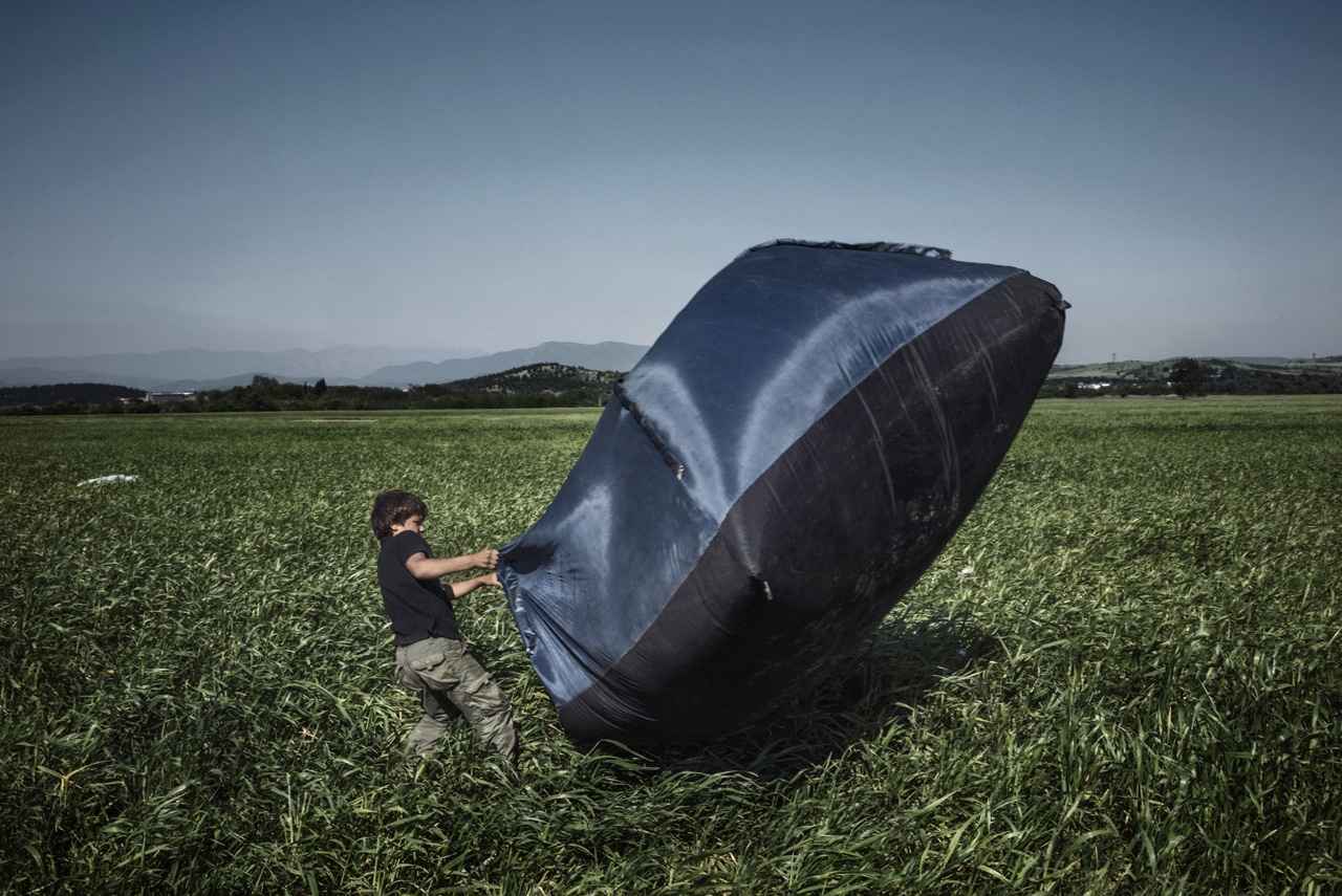 A refugee boy tries to stabilise his tent as the strong wind smashes down the tents at a makeshift refugee camp.