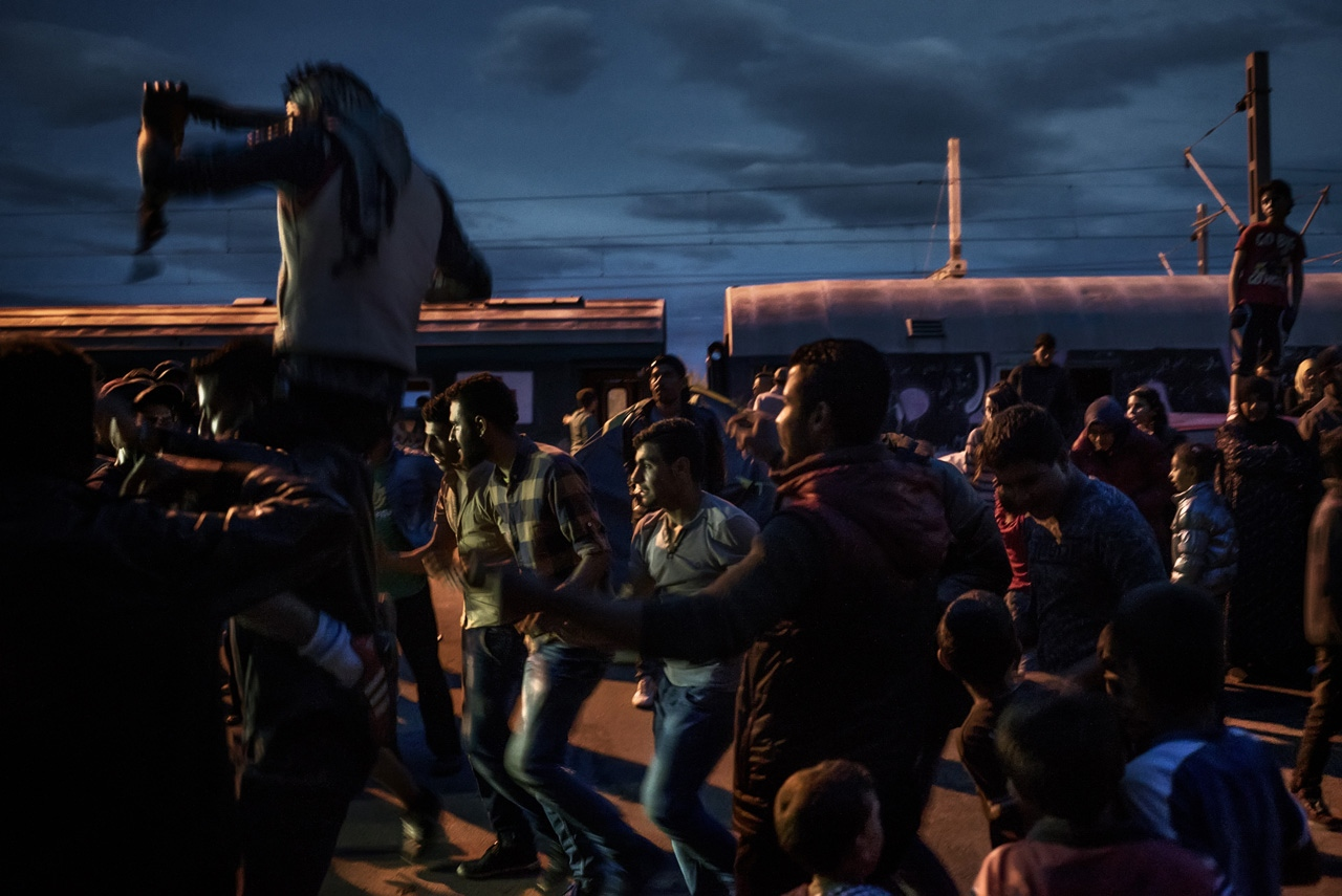 Refugee men dance at nightfall.