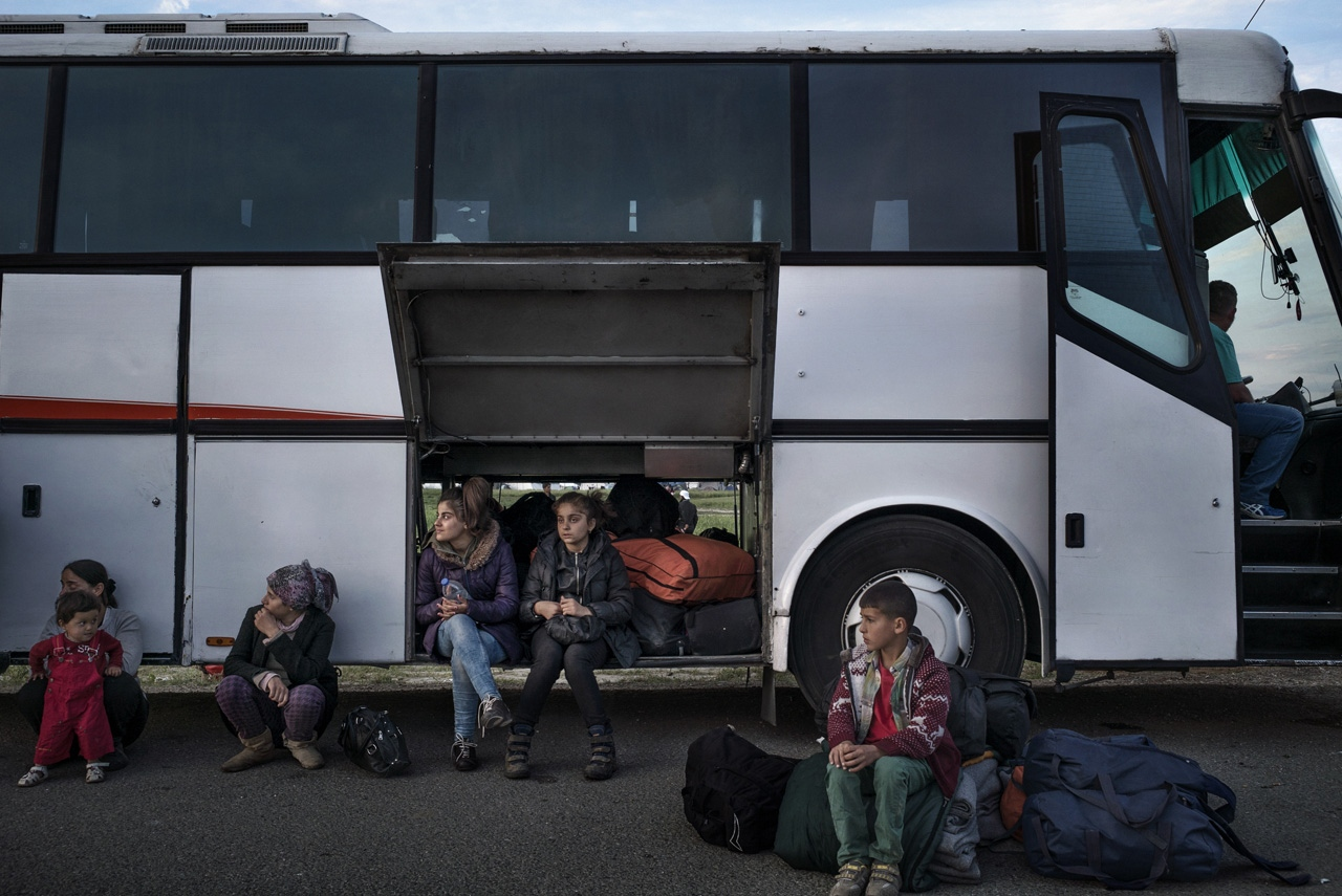 A refugee family waits outside a bus that will transport them and other refugees from Syria and Iraq to a relocation camp in Veria.