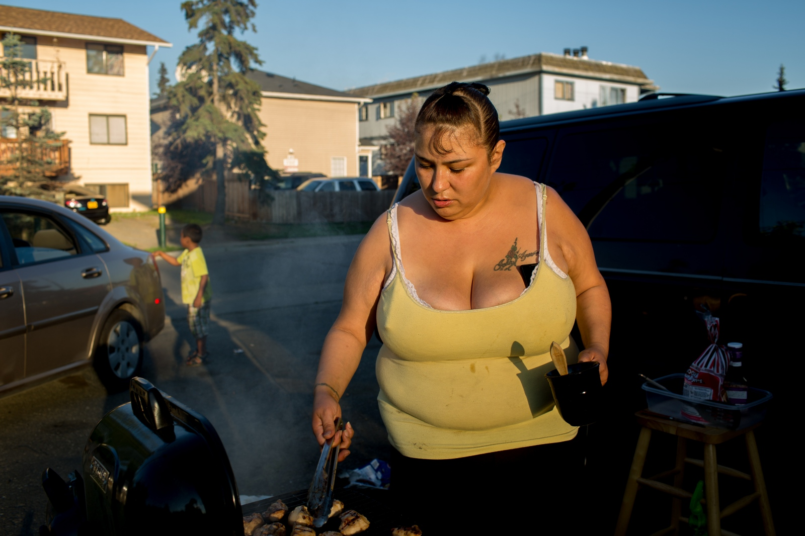 "Theresa Tunley grills food for her family on a warm night in the neighborhood of Mountain View in Anchorage, AK. ""If you look on my birth certificate, it says Hoyt Street,"" she says. ""I've lived here my whole life. People talk about the crime here, but I love it--I wouldn't live anywhere else."""