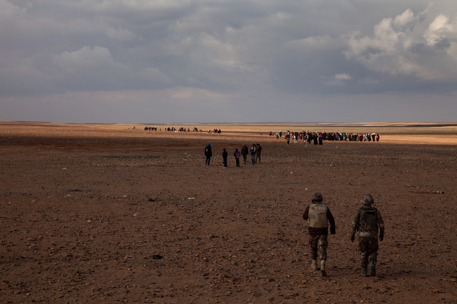 Jordanian troops prepare to help several hundred refugees crossing over the no man's land between Syria and Jordan. Over a thousand refugees crossed into Jordan that afternoon at a border crossing known as Al Hadalat,