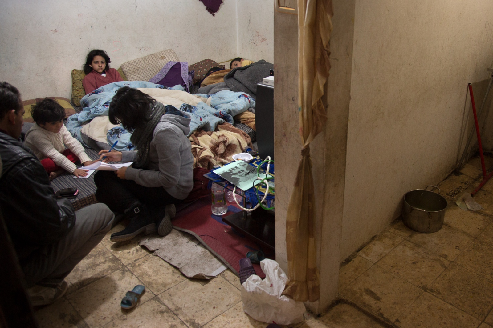 A UNHCR representative meets with a Syrian refugee family living in a basement to assess their needs. A majority of the refugees live hidden away in cities throughout Jordan.