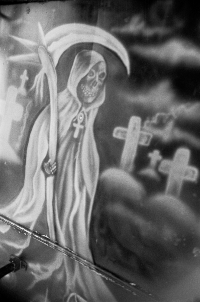"La Santa Muerte (The Saint of Death) is a symbol of the drug cartel era. It didn't exist when I lived here, but now it's everywhere - on trucks, Tshirts, tatoos, graffiti, statuary & so on. As the saying goes ""dios me proteje y ella me guia"" (""God protects me but she guides me"")"