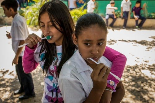 Two young teenagers brush their teeth during a demonstration by the local dental brigade from Central America Medical Outreach Feb 21, 2014 inMariposa Las Flores Lempira, Honduras. The dental brigade set up a temporary work space in a two room school in La Mariposa Las Flores Lempira, two hours outside of Santa Rosa de Copan. They also provide, gynecological, general medicine, and breast exams during other visits throughout Honduras. Photo Ken Cedeno