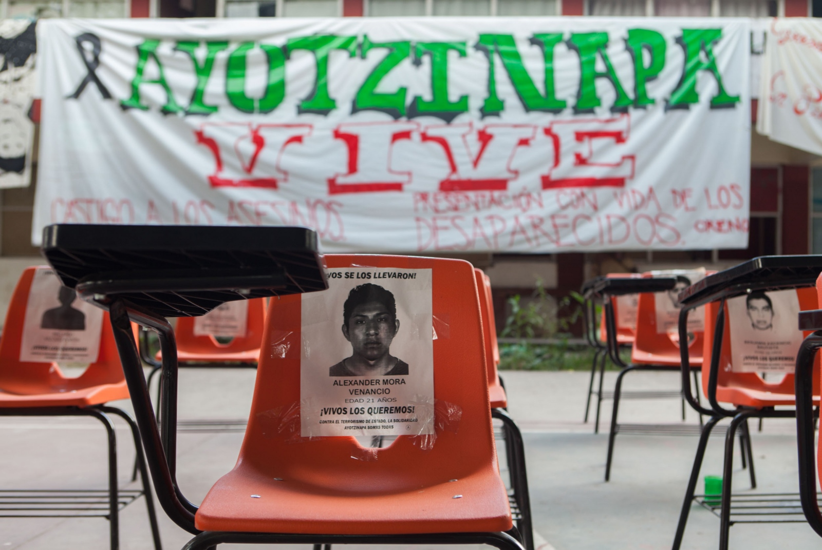 · Chair with the image of Alexandre Peña, the first student to be confimed dead among the remains found by the argentinian medical experts. One of the 42 school seats with images of the 42 dissapeared students and 4 murdered on september 26th, found in the basketball court of the school which has served as a reunion point, cafeteria and waiting lounge for the past 3 months. // · Silla con la imagen de Alexander Peña, el primer normalista a ser confirmado muerto entre los restos identificados por los peritos argentinos. Una de las 42 sillas de los normalistas desaparecidos y 4 asesinados el dia 26 de septiembre, que se encuentran en la cancha de basquetbol de la Escuela Normal Isidro Burgos, que ha servido como lugar de reunión, cafetería comunitaria, espacio de encuentros y de espera angustiante durante 3 meses.