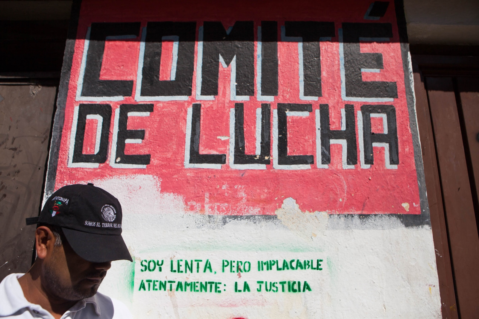 """Fighting Comitee"", area of the school where the students gather to learn about politics. A man who was helping out with the searches of the students stands by the bulding wearing a hat that reads ""We are the State worst enemies"" and text on the wall reads "" Im slow but relentless, att. the justice"". // Comite de Lucha es un espacio de la escuela en la que los alumnos se reunien para aprender sobre politica. Señor que estaba ayudando con las busquedas de los alumnos trae puesta una gorra que se lee ""Ayotzinapa: El terror del Estado""."
