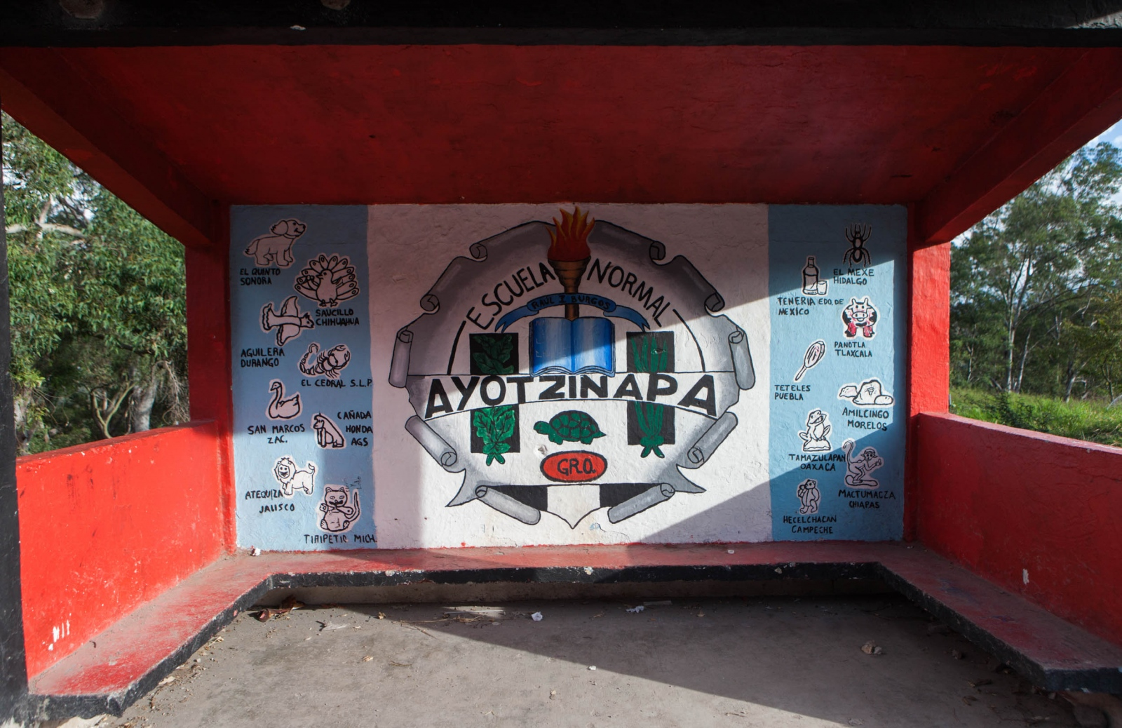 "Mural at the bus stop where the Normal Rural de Ayotzinapa Raúl Isidro Burgos school begins in the highway that connects the municipalites of Tixtla and Chilpancingo. The shields of the other 16 teaching schools are seen with the symbolic representation of elements that each region is known for. Ayotzinapa means in nahuatl "" River of turtles"". // · Mural en la parada de autobús donde comienza la Escuela Normal Rural de Ayotzinapa Raúl Isidro Burgos, sobre la carretera que une al municipio de Chilpancingo con el de Tixtla. Los escudos de las otras 16 escuelas normales rurales también están plasmadas con símbolos que representan cada una de sus regiones. Ayotzinapa quiere decir en nahuatl ""Río de Tortugas""."