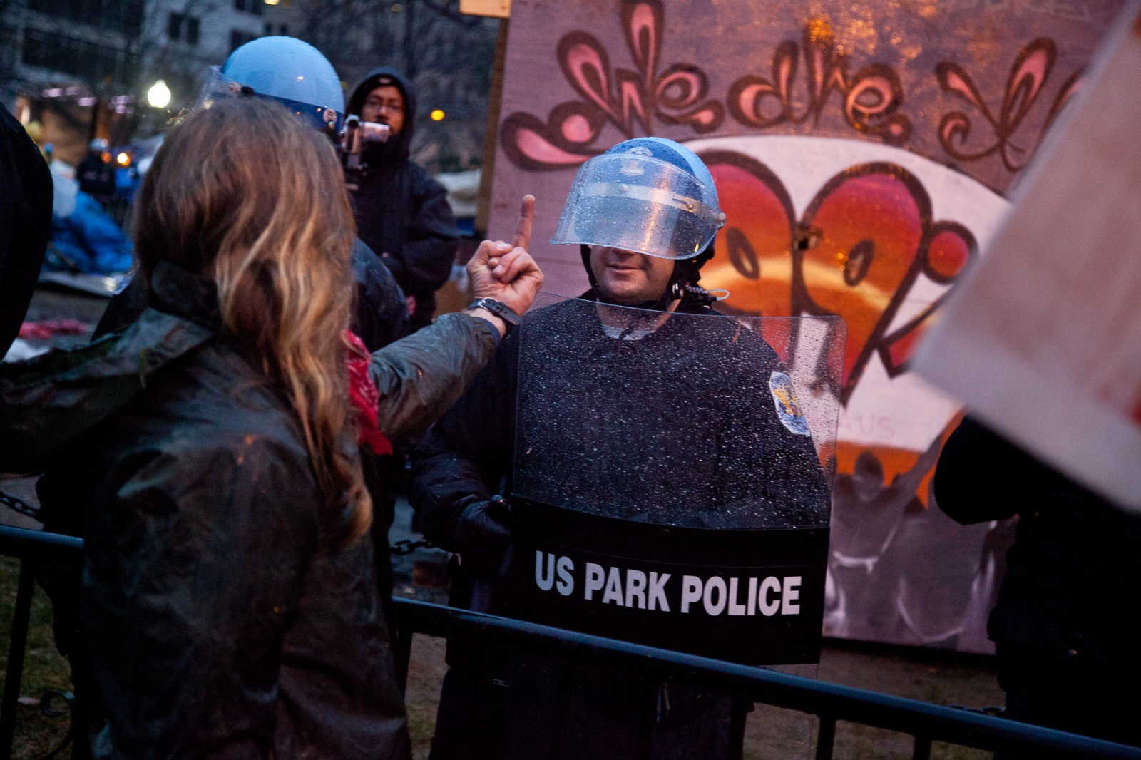 After being evicted from McPherson Square an angry protestor flashes the finger at a U.S. Park Police officer barricading the park.