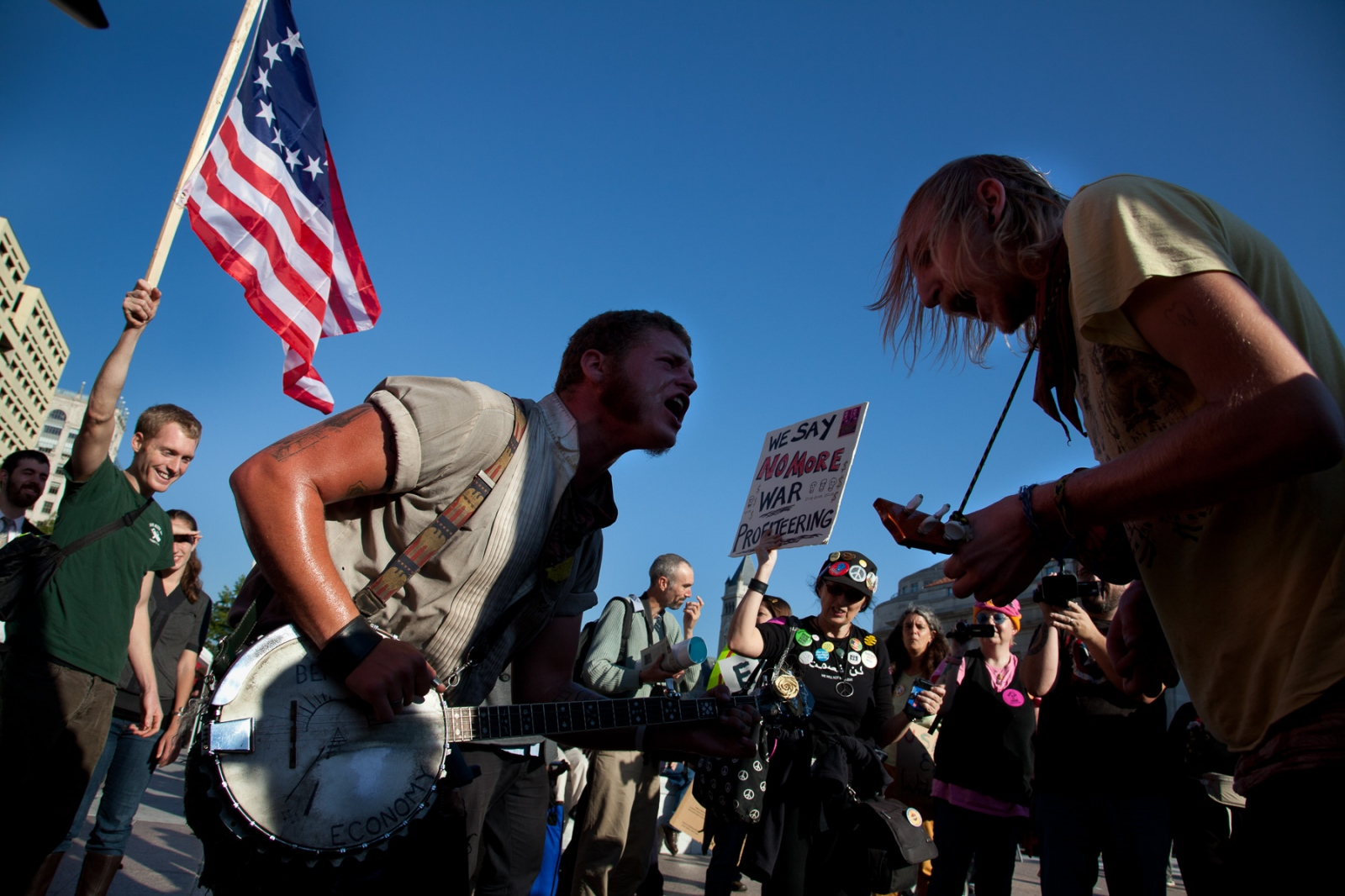 """Banjo Youngblood (left) and Jamie Troutman (right) sang the lyrics, """"the revolution has just begun,"""" to a boisterous crowd on Freedom Square during the first day of """"Occupy DC."""""""
