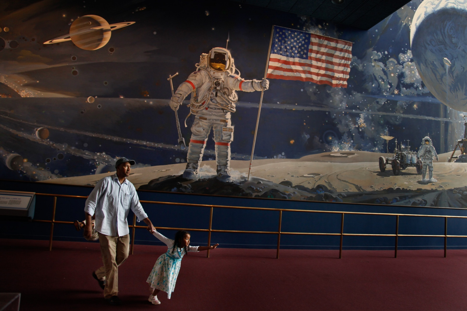 At the National Air and Space Museum a father walks his daughter past a mural showing the landing of Apollo 11 on the moon