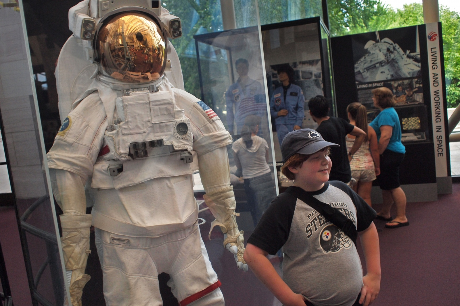 A young boy poses in front of a space suit worn by astronauts on the U.S. shuttle during the 40th Anniversary of the Apollo 11 mission that landed the first humans on the moon.