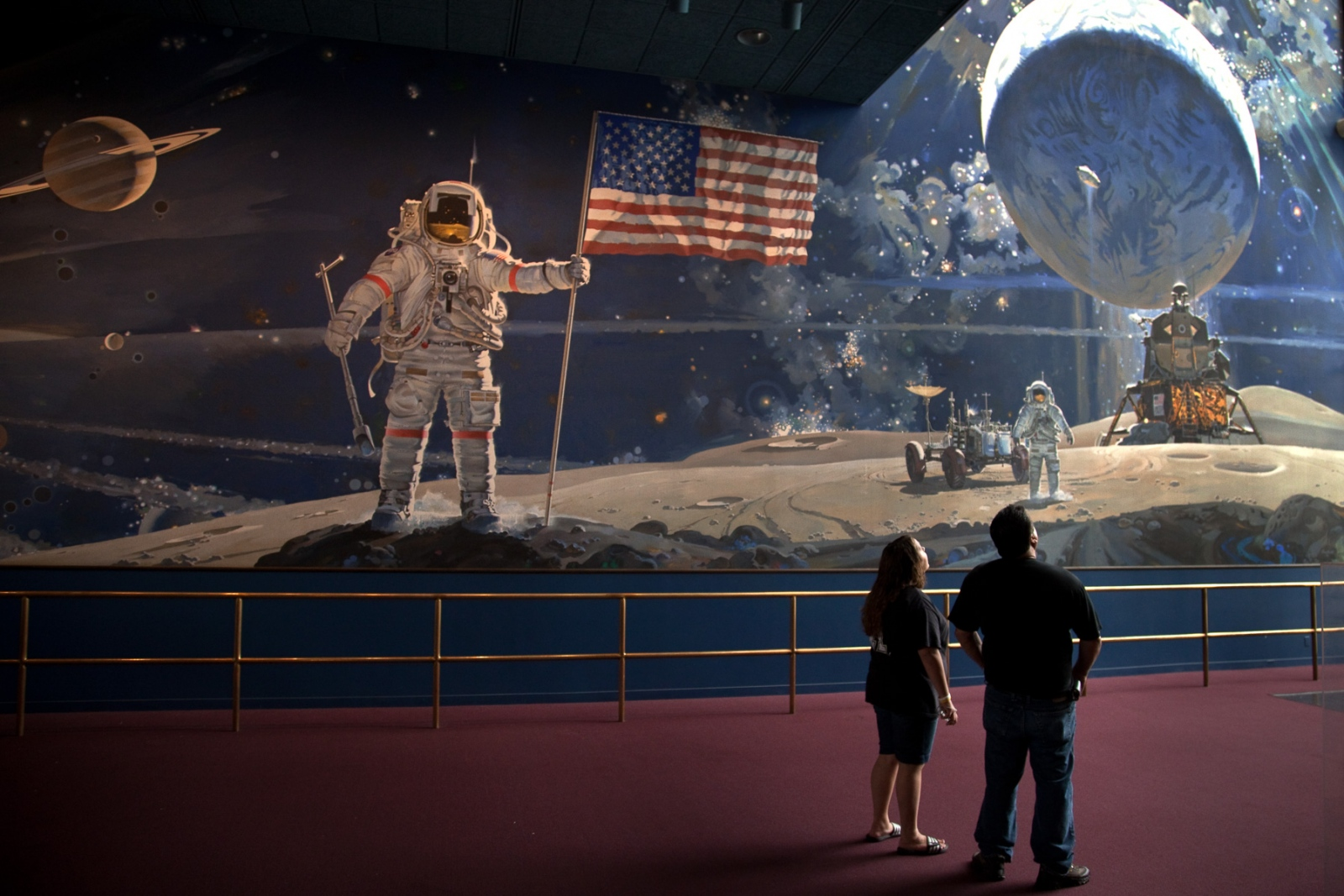 Visitors stand next to a mural showing the landing of Apollo 11 on the moon during the 40th Anniversary of that historic moment what landed the first humans on the moon.