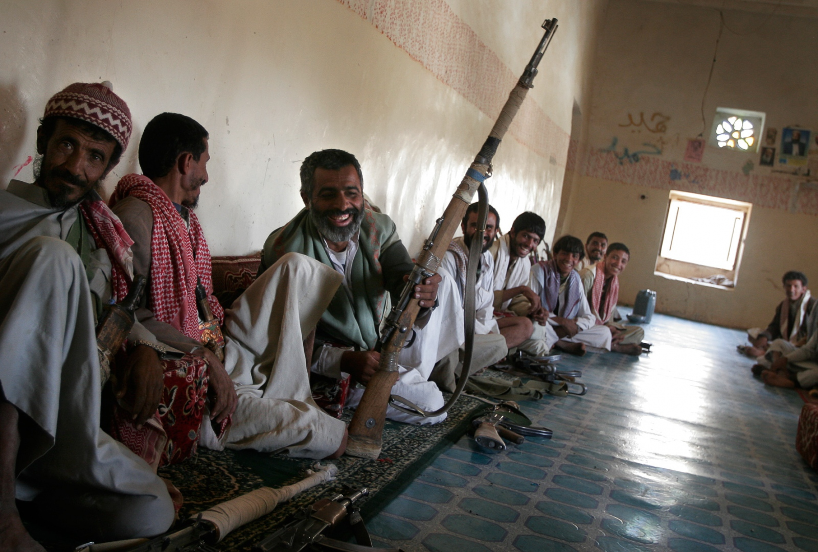 Tribesmen admire the sniper's rifle of Saleh Ali al-Hadj (far left) as they wait to meet and lunch with Sheik Rabea.