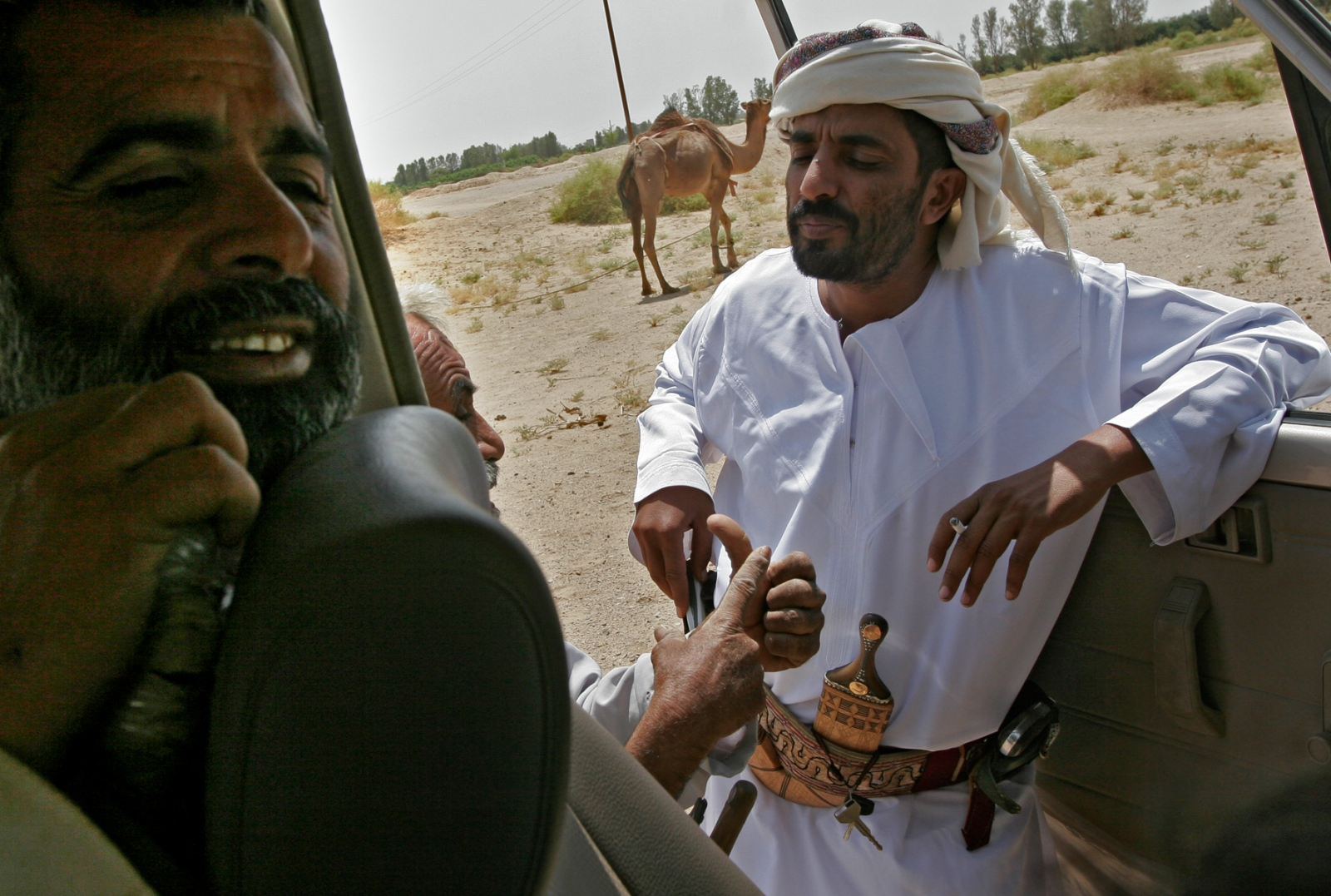 """One of Sheik Rabea's guards listens as a tribal member complains that Rabea should not be hospitable with Americans. One person told him """"the U.S. will do to Yemen what it did to Iraq."""""""
