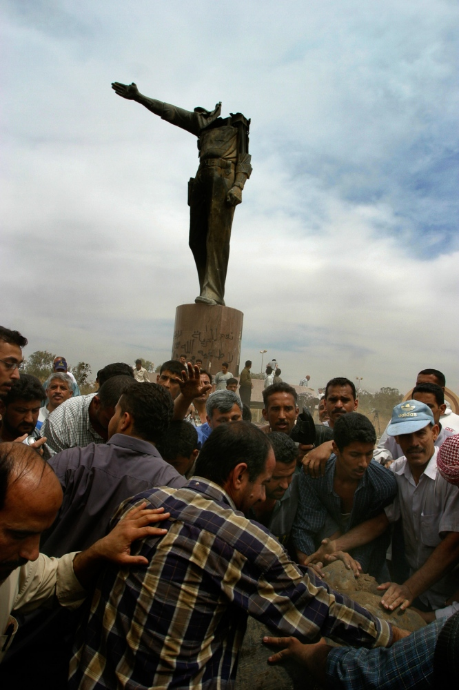 Iraqis manage to tear off the head of Saddam Hussein from the largest monument of him in Baghdad. Many Iraqis were thrilled that Saddam was gone, but distrustful of American intentions.
