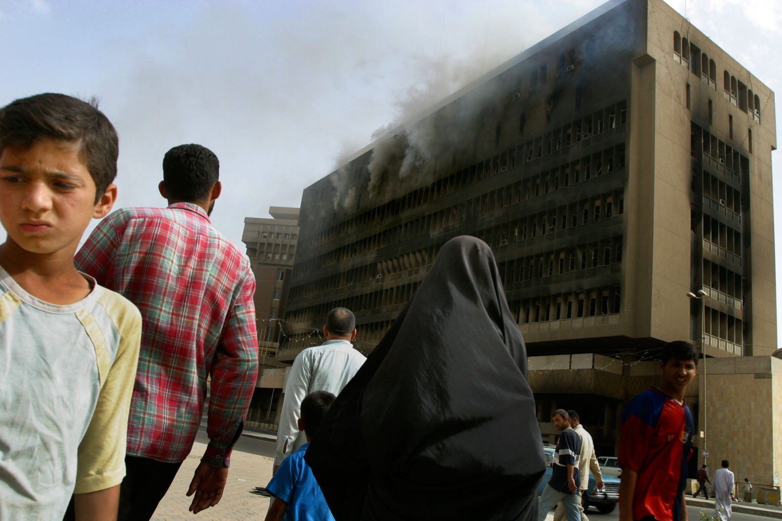 Iraqis are in shock as they walk in downtown Baghdad and find many of its buildings smoldering from looting by locals.
