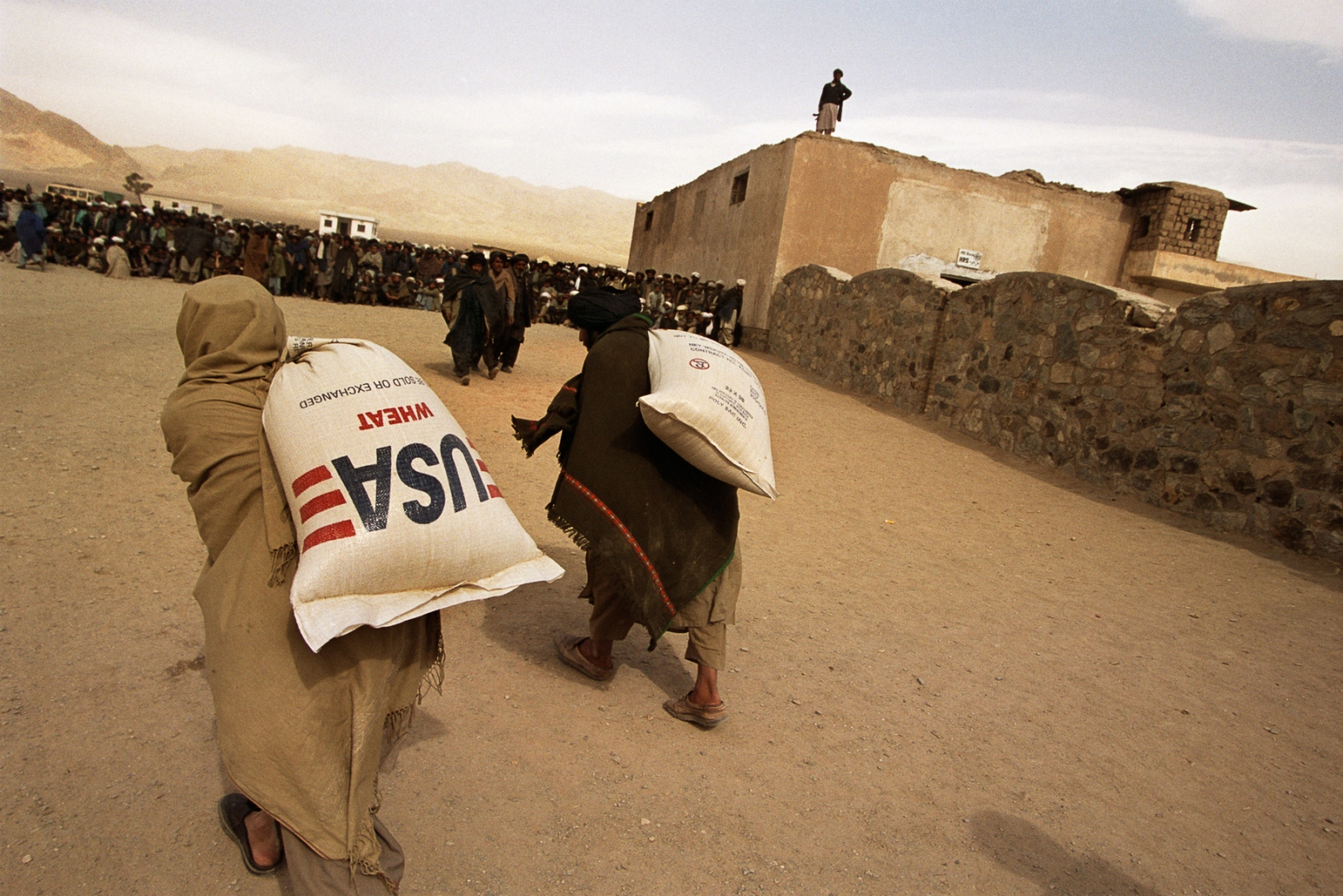 Refugees carry 110-pound sacks of wheat from the distribution center to their tents, a monthly allotment from the World Food Program, which is hindered by the absence of donors.