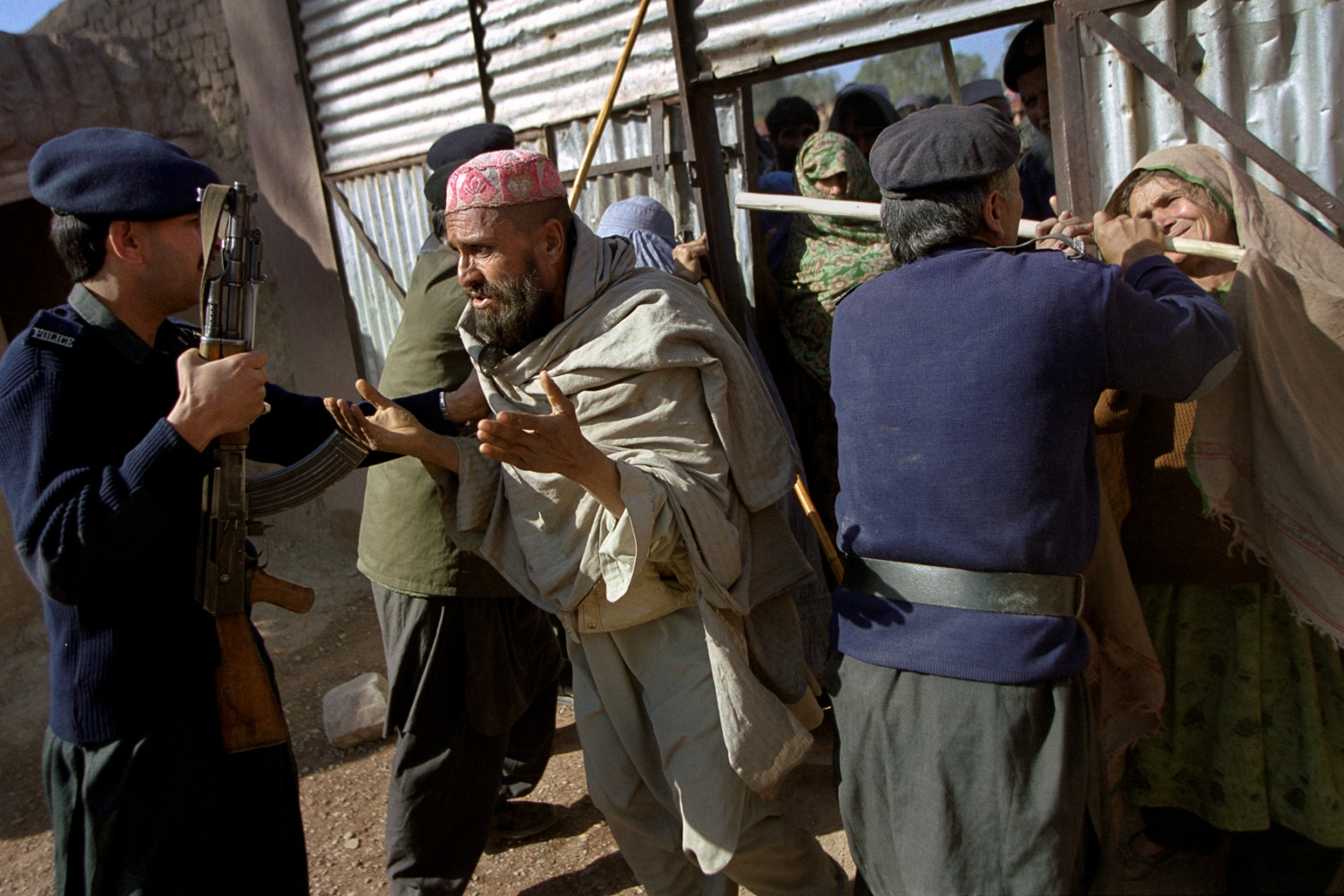 Pakistani guards at Jalozai hold back refugees who are trying to push their way into a compound holding bags of donated flour. The Afghans in the camp have little access to food.