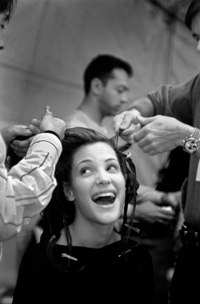 Several stylists may be required to execute a single, complicated hairdo. Two stylists work on model Tereza Makova. Hair and makeup problems, a late model, or an indecisive designer can delay a show up to one hour and throw off the entire day's schedule. Nicole Miller, fall '93.