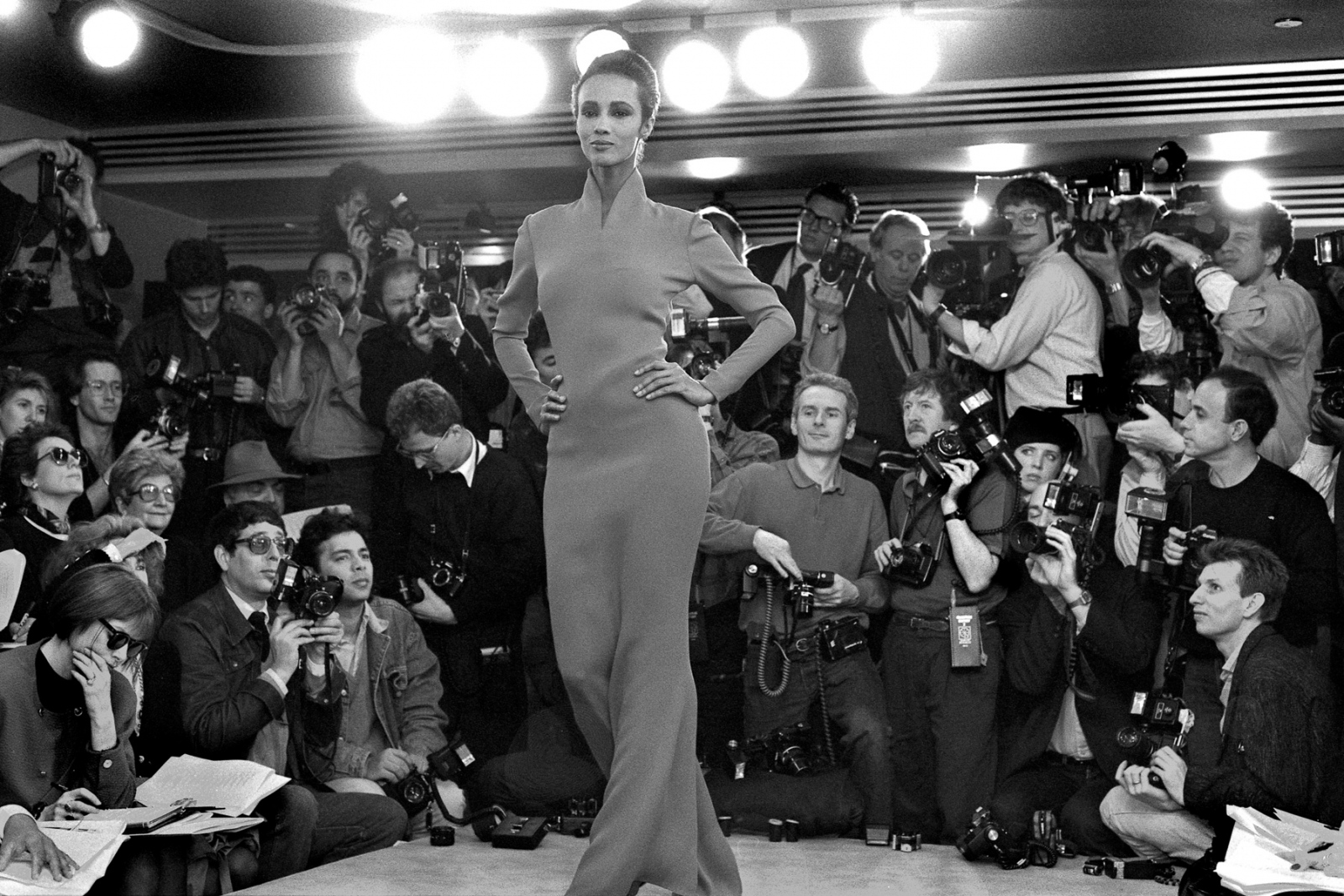 "In pre-Bryant Park days, many designers presented their collections in the cramped confines of their showrooms. Not all guests were seated. Some were regulated to ""standing room."" Here, model Iman walks the runway in Klein's showroom. Calvin Klein, spring '87."