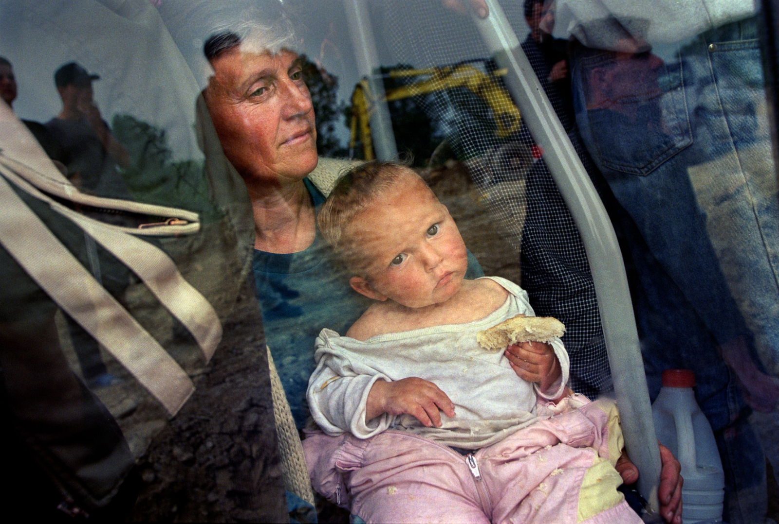 A mother and child wait to be bused to Senokos refugee camp in Macedonia after fleeing the war in Kosovo.