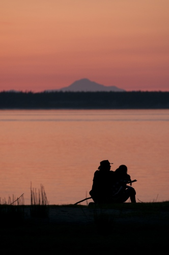 A young couple watches the sunset from earthquake park in Anchorage, AK looking out over Cook Inlet and Mt. Denali. Photo Ken Cedeno