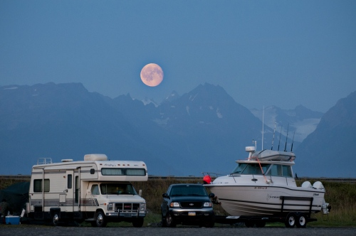 An almost full moon rises above Homer, AK as campers set up near the beach on the Homer Spit in Homer, AK August 7, 2009.