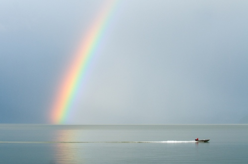 A boat travels across the water beneath a giant rainbow off the shores of Wrangell, Alaska, October 1, 2009.