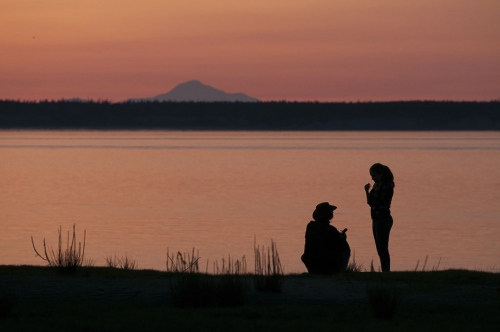 Mount Denali looms in the background during a sunset as a couple stands at the edge of Cook Inlet in Earthquake Park in the west part of Anchorage, AK August 2009.