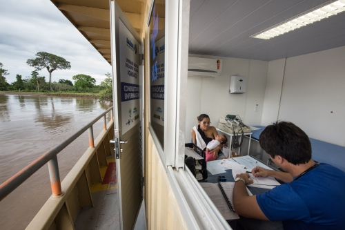 Doctor Luiz Pessoa talsk to a patient in his office aboard the Igaracu in an indigenous community on Rio Madeira, June 23, 2015. Doctors and dentists working with the  Basic Health Unit River (BFHU) system, provide primary care visiting indigenous communities via the   Igaracu, a boat outfitted and designed to provide medical and dental assistance. They v isit these communities during a 20 day period up and down parts of the Amazon river and its tributaries. The Igaracu is the first government subsidized medical boat for Brazil.