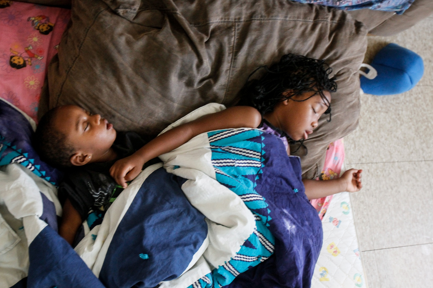 Cousins Marcus Hill and De'Niyah Patrick sleep on a mattress on the of De'Niyah's mother's apartment in the Brand Whitlock Homes on Friday, Nov. 18, 2011.