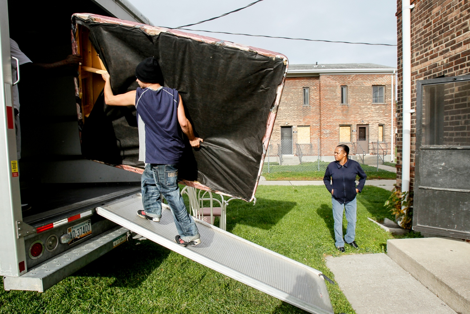Casandra Cofie watches as Donald Smith carries a mattress out of her daughter, Kasandra Cofie's, apartment in the Brand Whitlock homes on Monday, Nov. 21, 2011.