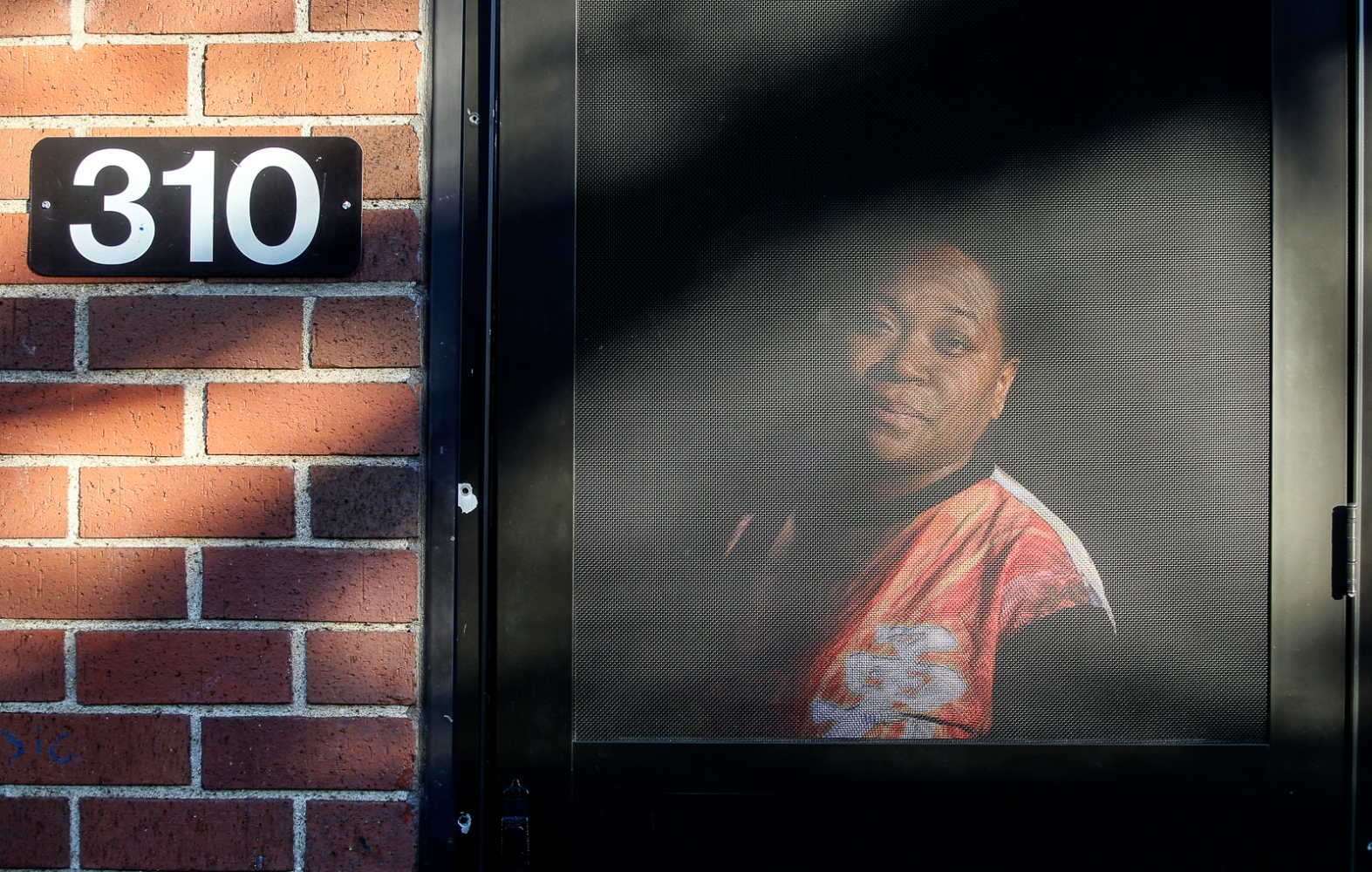 Tennille Ben looks out of her door at the Brand Whitlock homes on Friday, Dec. 2, 2011.