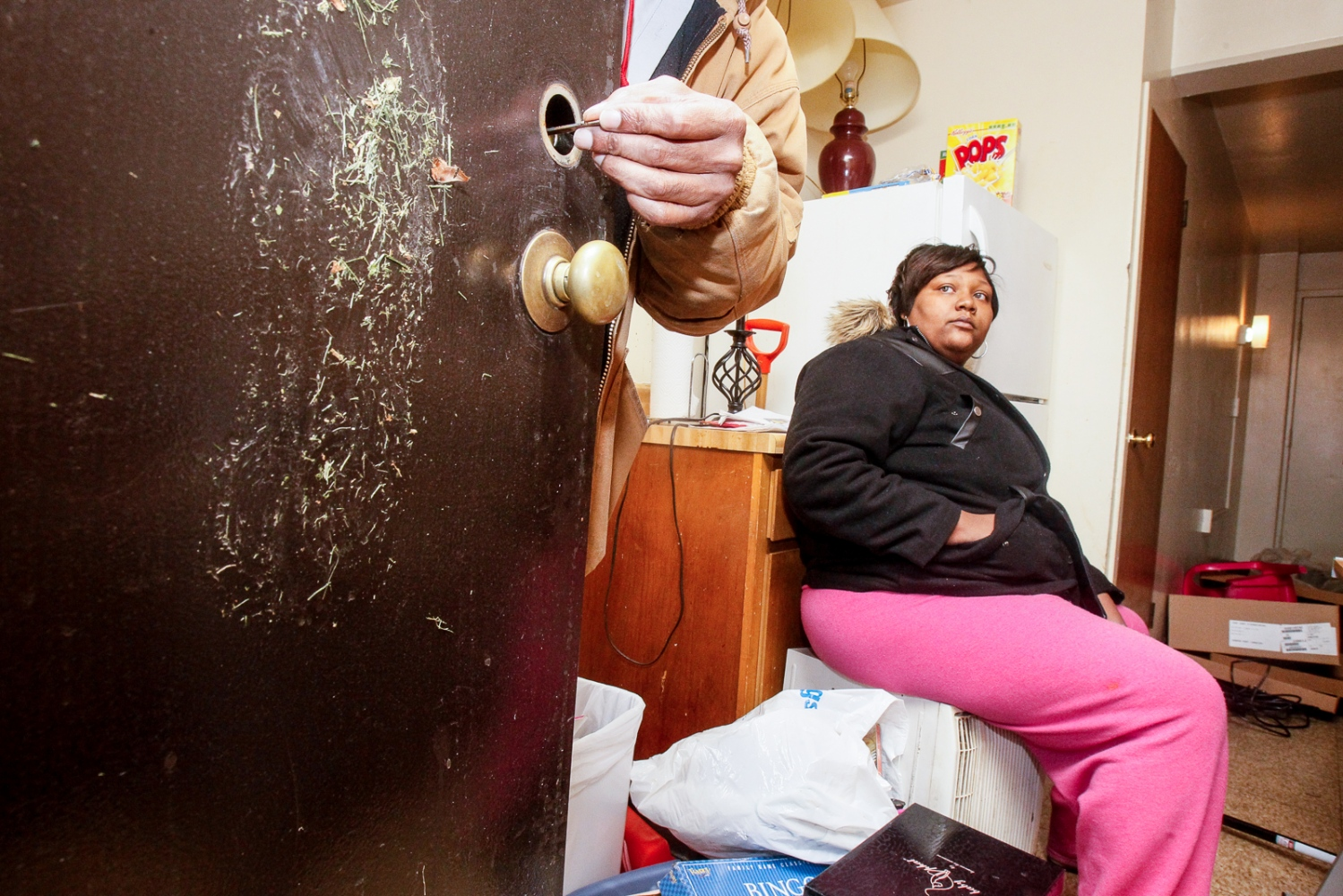 Tierra Nelson watches as a maintenance man repairs her back door on Sunday, Dec. 11, 2011 after burglars kicked in the door while she was gone.