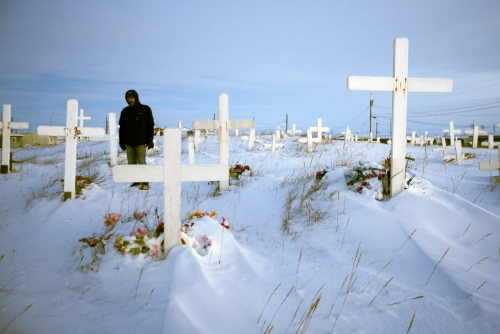 A resident of Shishmaref visits his sister's grave on the 17th anniversary of her death. The cemetery is centrally located in front of the Lutheran Church - The only church in the village.