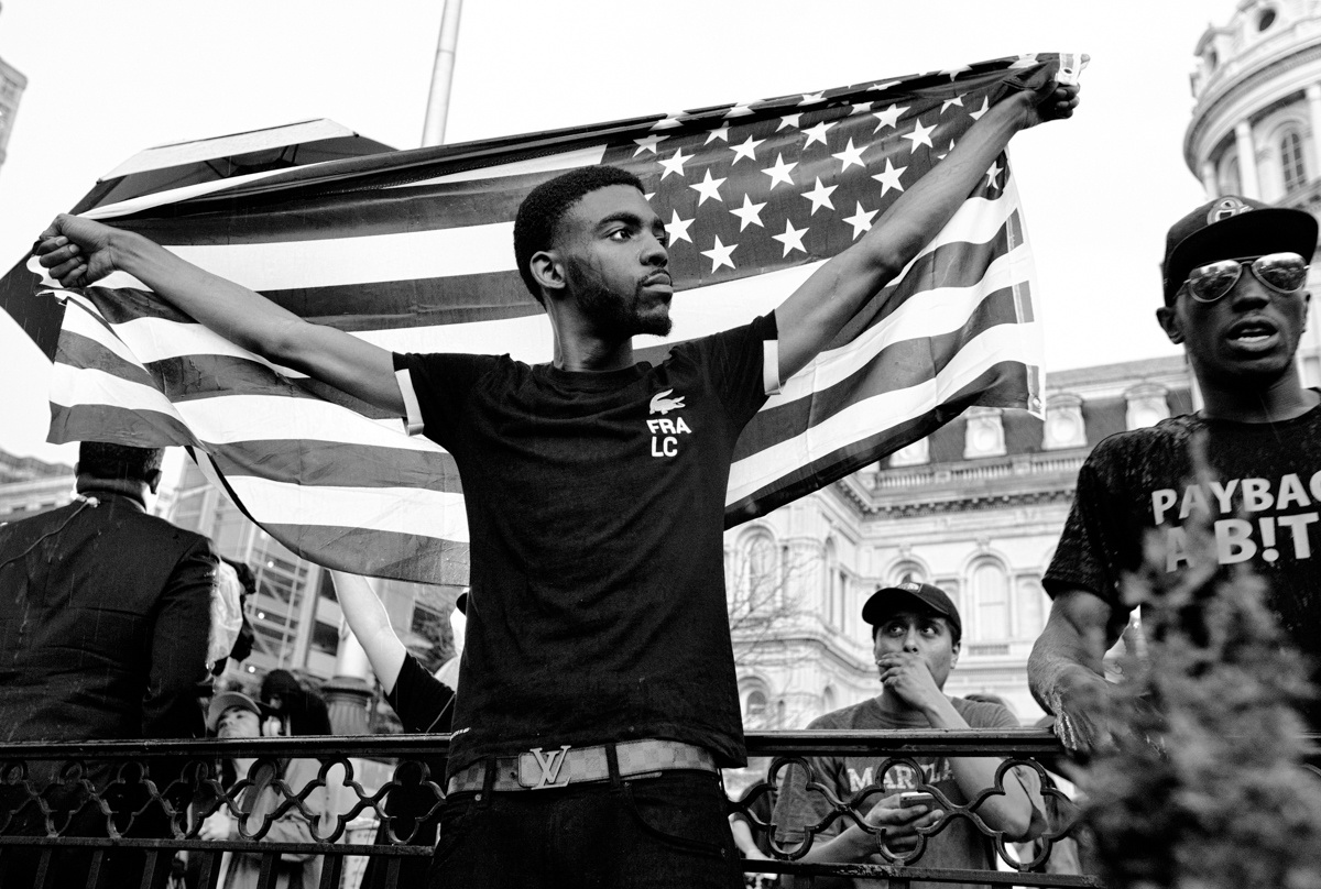 Baltimore, Md- A young protester holds the American Flag during the March For Peace.
