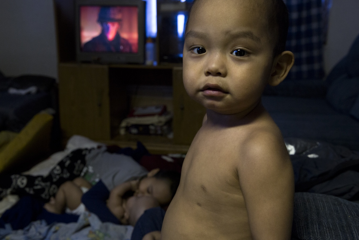 Ryan Ningealook, 4, looks on while his two brothers slept on the floor in the only room in their small home in Shishmaref, Alaska.