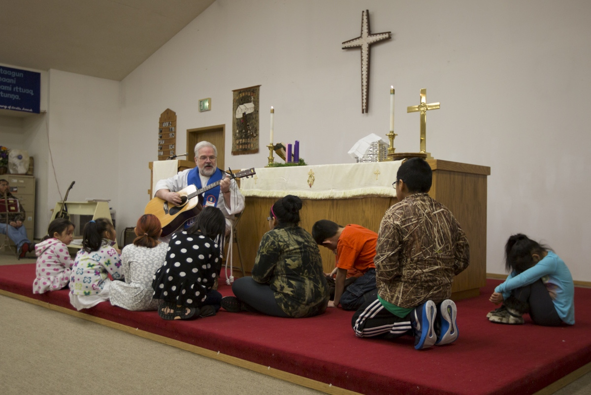 Although most residents of Shishmaref are officially members of the Lutheran Church (the only church in the village), they also observe and respect their traditional Eskimo practices and beliefs. During the Sunday service, Pastor Marvin Jonasen sings to the children as part of his sermon.