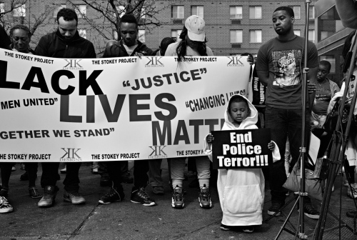 Baltimore, MD- A young protester holding up a sign during a moment of silence in honor of Freddie Gray.
