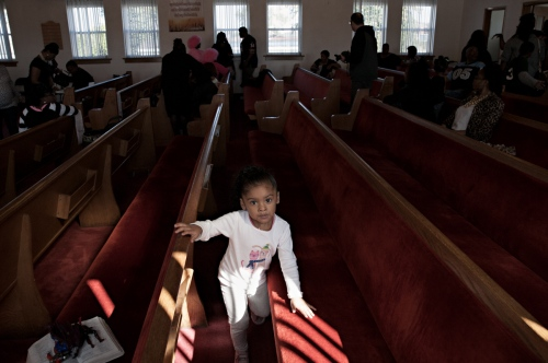 A young church member plays in the pews at First Mission of Jesus Christ Church in East Chicago.