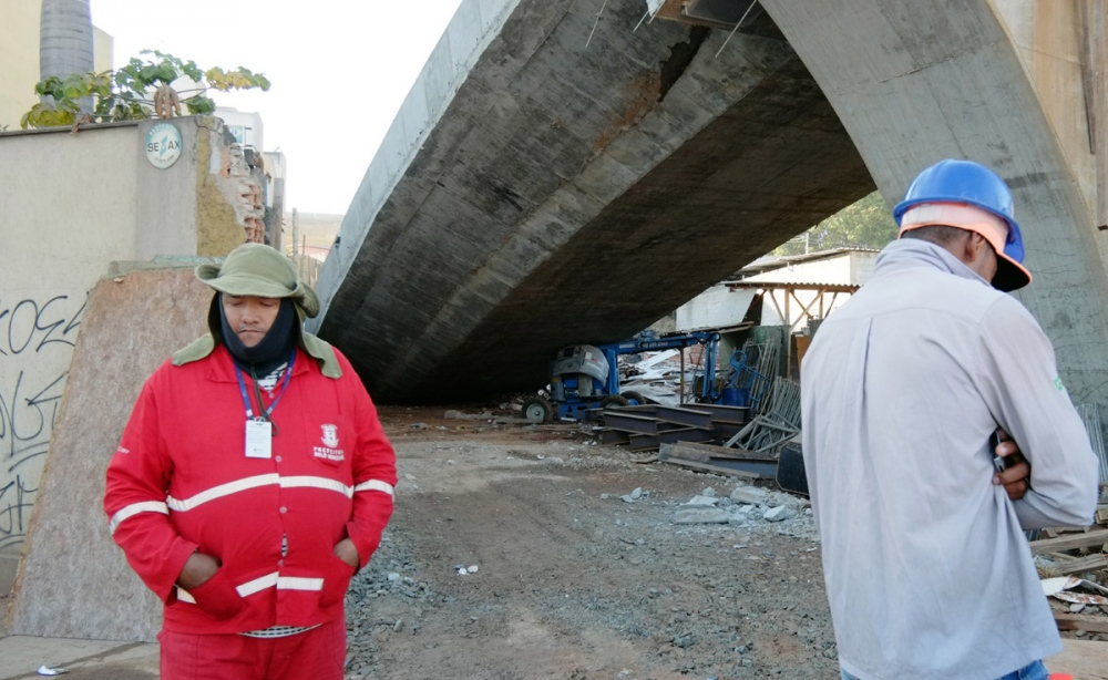 Unidentified workers stand near an unfinished overpass that collapsed in the Brazilian World Cup host city of Belo Horizonte leaving at least one person dead and casting a shadow over a tournament that has suffered repeated construction accidents and delays. The bridge, located about two miles from the Mineirao Stadium where World Cup games are being played, collapsed as vehicles were passing on a busy road underneath.
