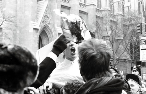 Members of the Group Act-Up burn a bible outside New York's St. Patrick's Cathedral to protest church policy towards AIDS.