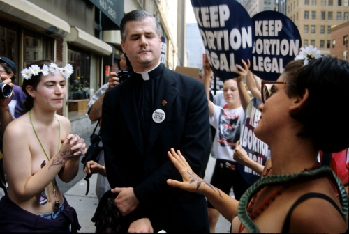 An unidentified priest reacts to topless women protesting a proposed law to make abortion illegal in Midtown Manhattan.
