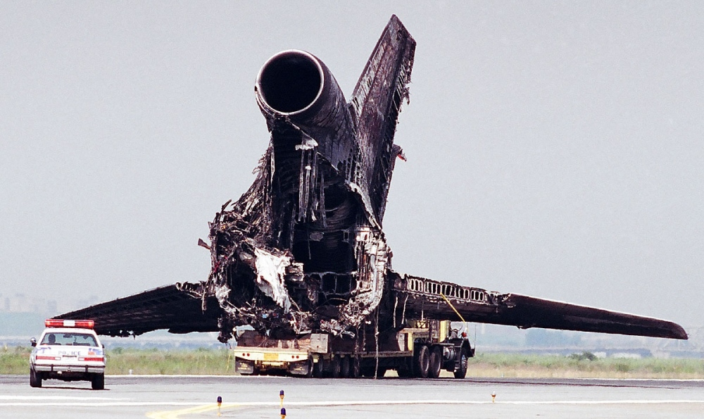 Workers remove the remains of a Lockheed L-1011 TriStar airplane that caught fire while departing for San Francisco and aborted the takeoff shortly after liftoff. There were no fatalities among the 280 passengers, although the aircraft was destroyed.