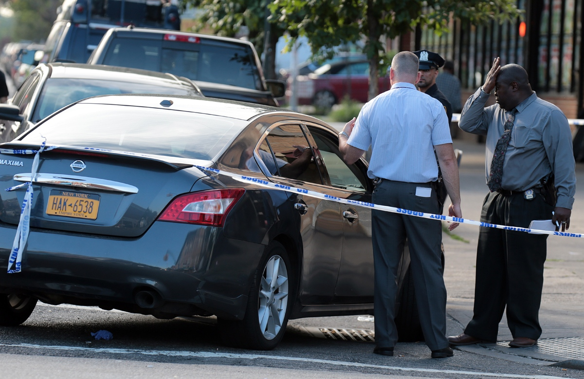 A seasoned NYPD detective (R) from the 114th Precinct in Astoria, Queens react to a shooting evidence inside a Nissan Maxima at 28th Ave and Steinway Street early Sunday morning.