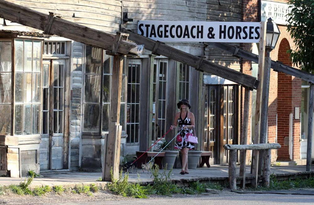 A young woman walks her dogs on the very much alive ghost town of Virginia City, Montana. Frozen in time, it is a remarkably well preserved old west Victorian gold mining town.