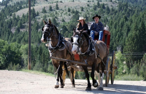 Ty Morgan and Rachel Billings rides a stagecoach on the very much alive ghost town of Virginia City, Montana. Frozen in time, it is a remarkably well preserved old west Victorian gold mining town.